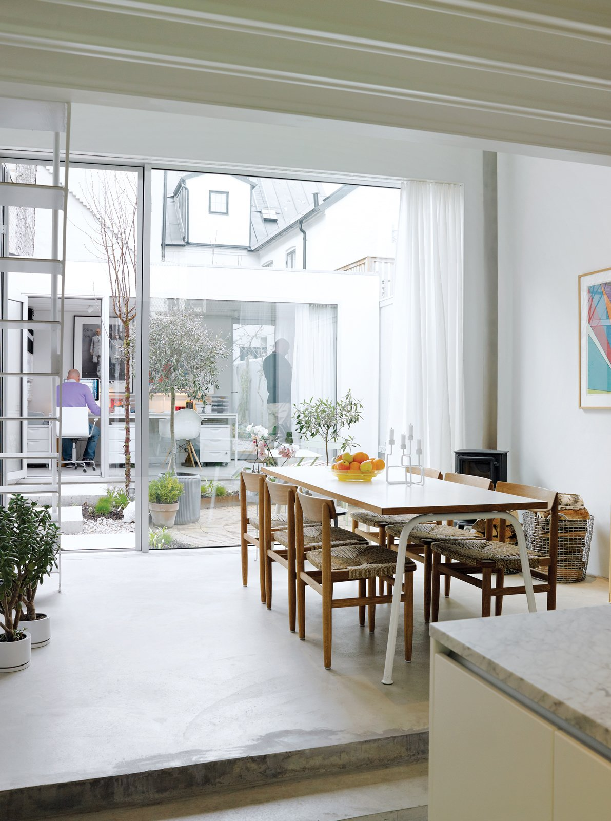 Dining Room, Table, Chair, and Concrete Floor The view from the kitchen is as lively as it is light, taking in the dining area, tiny courtyard garden, and the separate office building backed by the jumble of old buildings to the rear. The rustic dining chairs are by Börge Mogensen from Karl Andersson & Söner.  Photos from Contemporary Nordic Town House