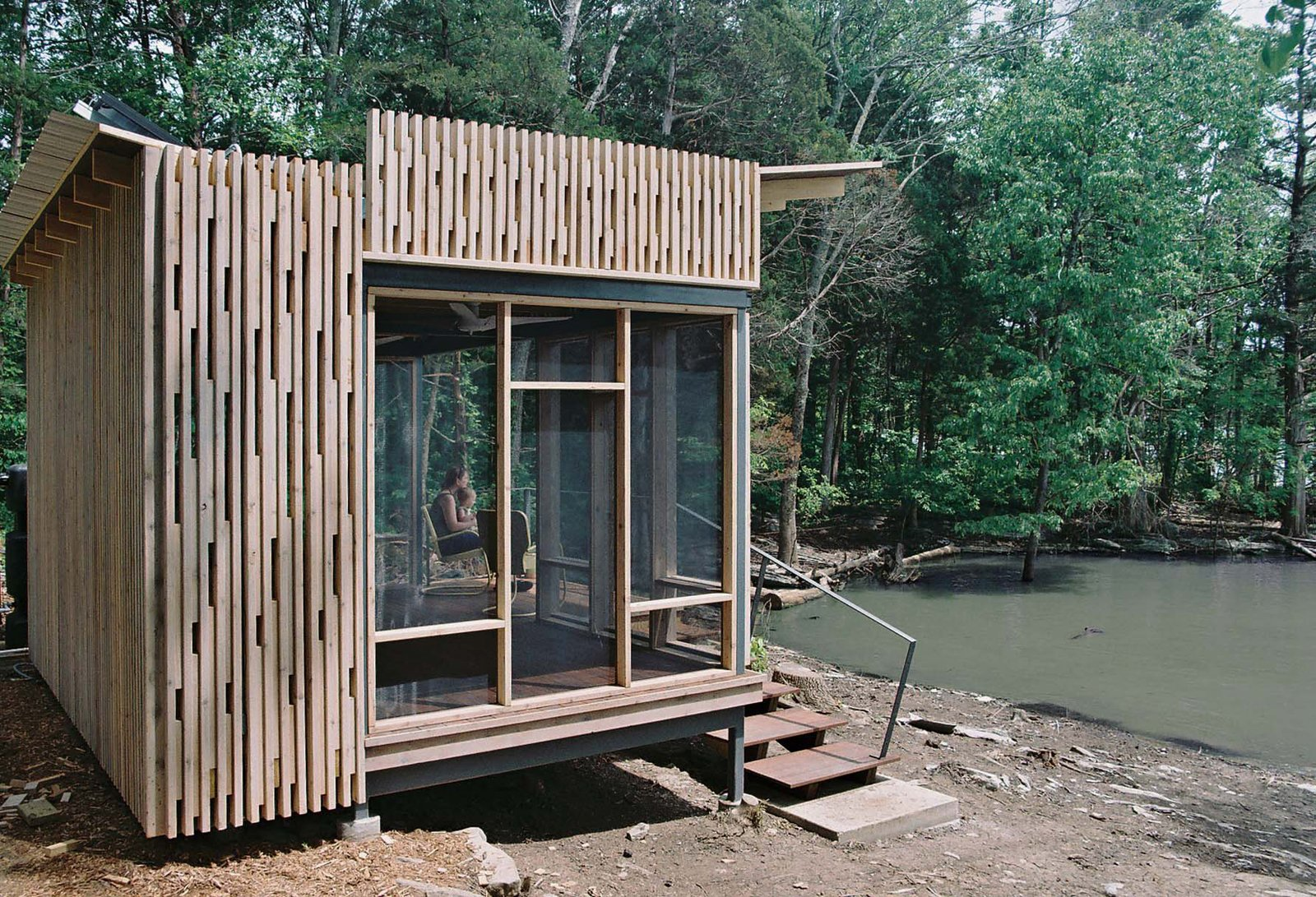 """Exterior, Cabin Building Type, and Wood Siding Material For the Knoxville-based CEO of environmentally-focused marketing firm the Shelton Group, building an off-the-grid lakefront pavilion in Sharps Chapel, Tennessee, wasn't so simple. With the help of architect Brandon Pace, she built a small prefabricated cabin on a """"funky piece of property"""" on Norris Lake, a man-made reservoir.  Photo 4 of 4 in How to Build an Off the Grid Cabin"""