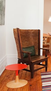 Building on contrasts, Jones juxtaposes a modern two-toned side table alongside an antique armchair.