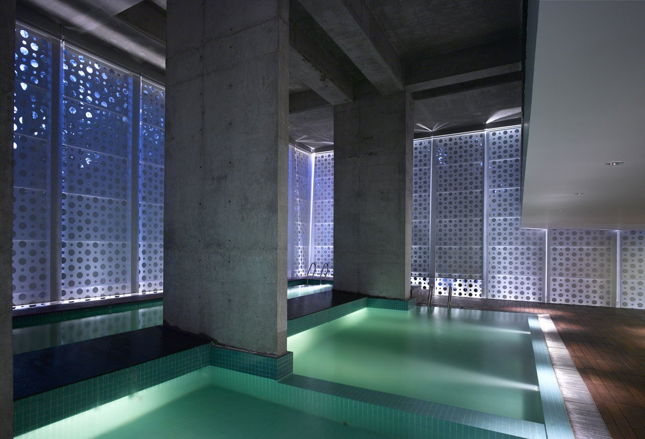 """An interplay of geometries in what Khanna calls """"the belly of the building."""" Uplights create new angles of light, raw concrete retains a rough edge and square pool tiles add texture and color while offsetting the perforated circles. The dropped ceiling at right is part of a small balcony overlooking the pools; beneath it is a sitting area.  Photo 13 of 17 in A Modern Aesthetic in Mumbai"""