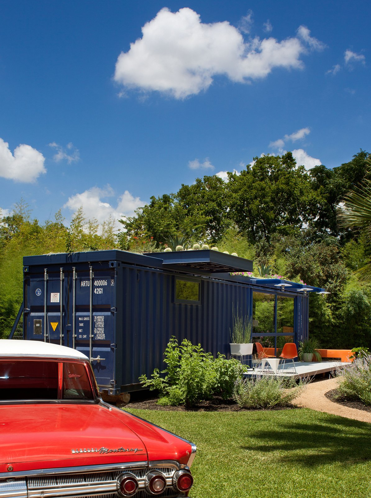 Exterior, Shipping Container Building Type, and House Building Type Hill's 1962 orange Mercury Monterey complements the blue of the container, whose original opening was retained on one end as the entrance to the garden storage shed.  Photo 5 of 17 in Smaller in Texas