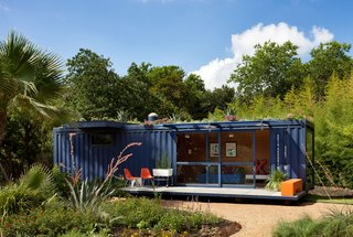 While shopping for containers, owner Stacey Hill was instantly drawn to this one's existing blue color and chose to buy it and leave it as is. Architect Jim Poteet added floor-to-ceiling sliding doors to allow light in, as well as a cantilevered overhang to shade a window on the left side, which houses a small garden storage area.