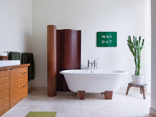 The master bathroom has a bamboo screen and a Deauville tub by Victoria + Albert. A vintage enameled metal sign from the London Underground is framed by the screen and a cactus that sits atop an African stool.