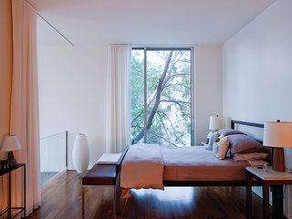 A pair of mid-century Martz lamps flank the Parsons bed from Room & Board in the master bedroom.