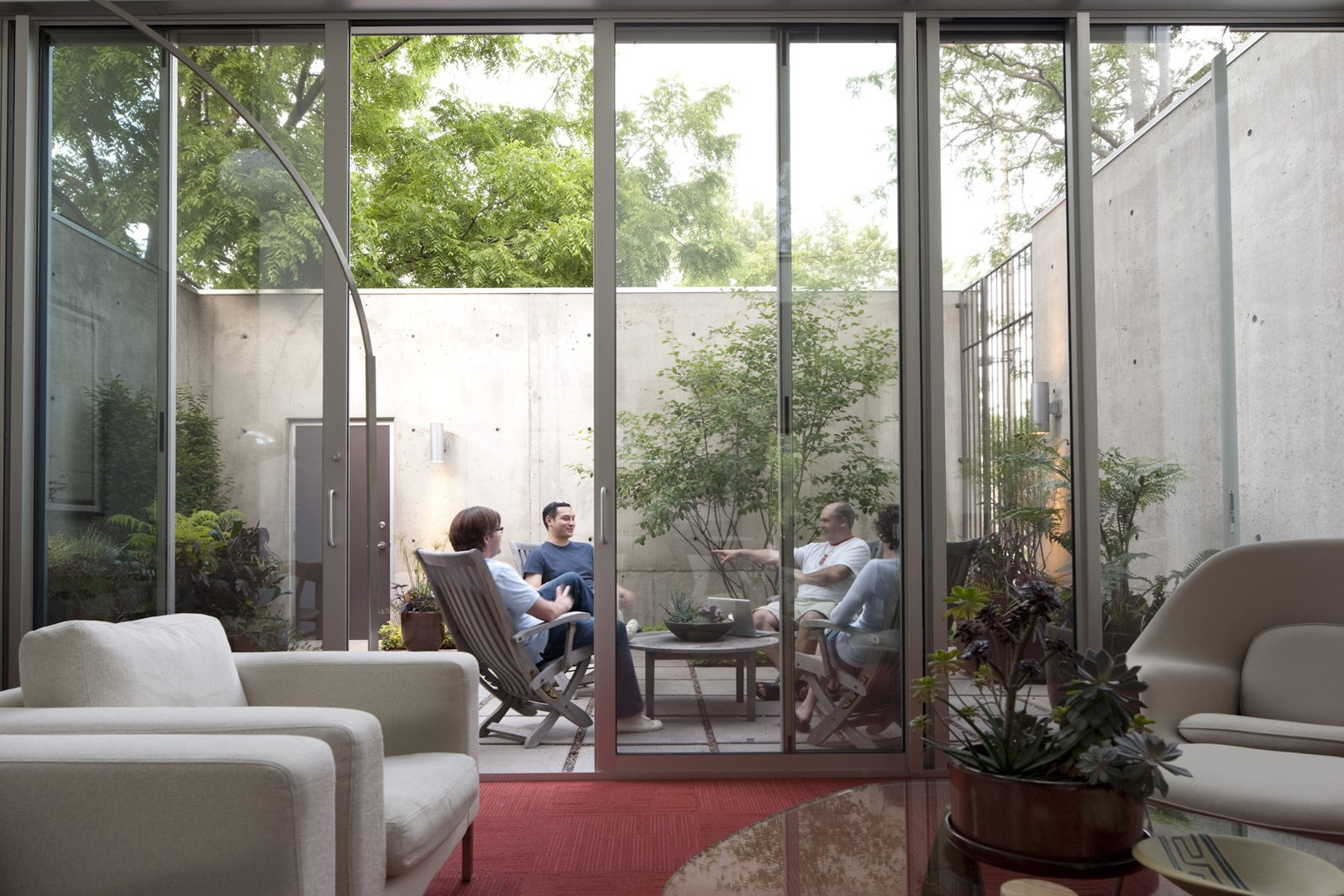 Friends gather in the courtyard to make the most of Minneapolis's limited temperate times.  20 Homes with Inspiring use of Glass by Diana Budds from Modern Urban Retreat in South Minneapolis