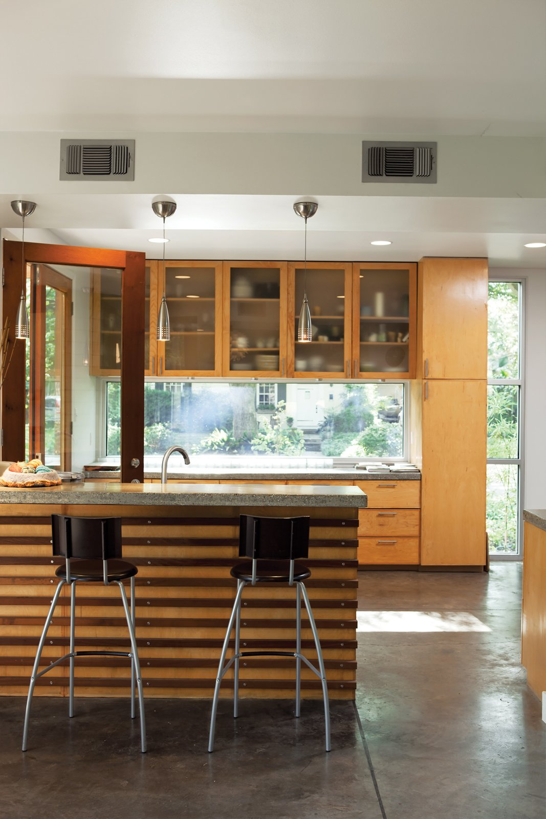 Kitchen, Concrete Floor, Wood Cabinet, and Pendant Lighting Moreland House  Photo 6 of 13 in Designed to Handle the Heat and More