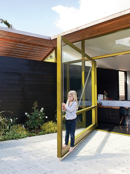 Conceived as a glass wall or window that could swing open rather than a typical door, the resulting glass-and-metal piece is so heavy that it required its own foundation! Thanks to clever engineering by Sand Studios, even seven-year-old Macy can operate the 2,000-pound door.