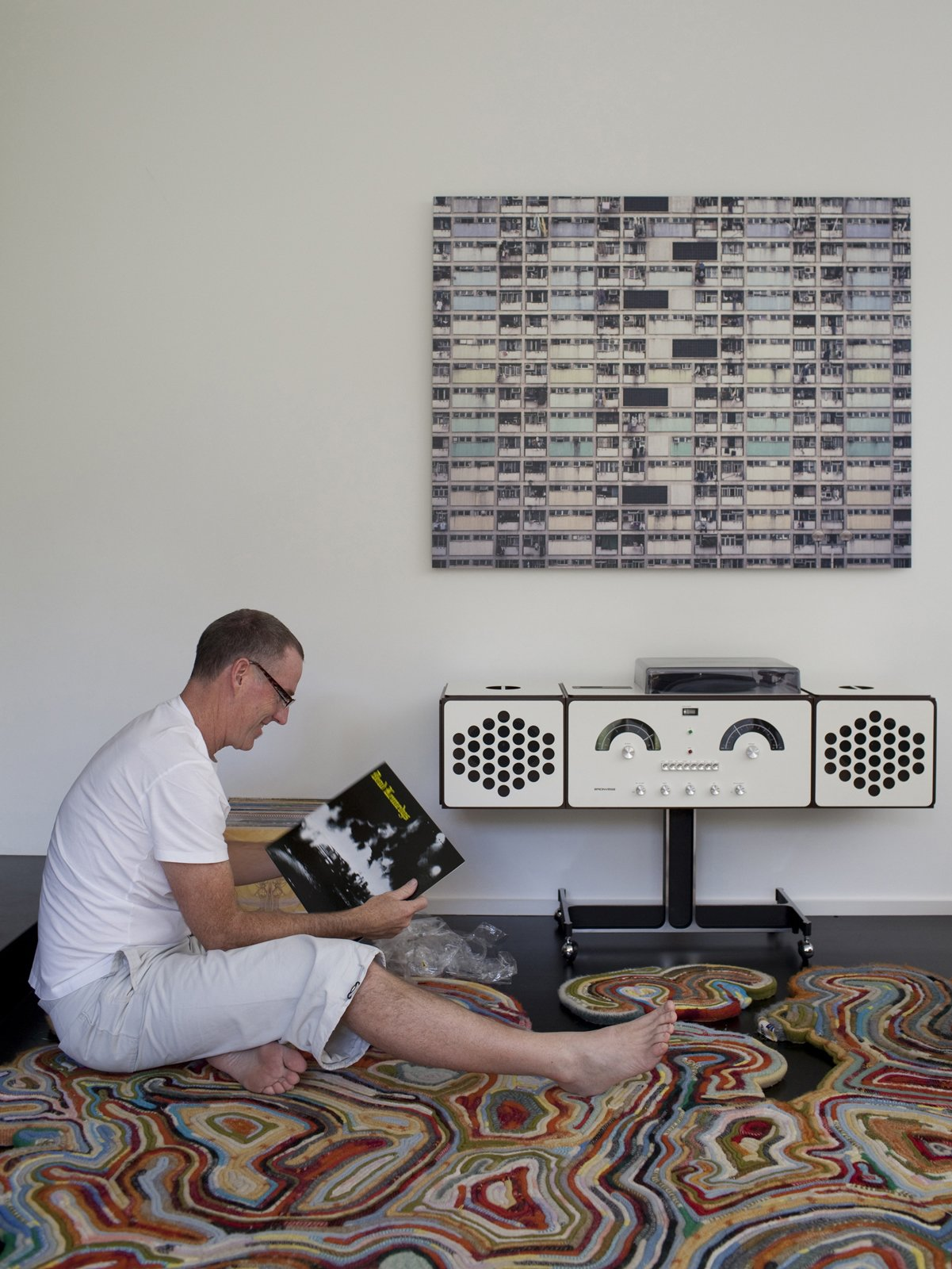 Sitting on the Recycled Blanket Rug by Tejo Remy and Rene VeenHuizen, Chris digs through his records looking for something to play on the new Brionvega RR226 by Achille Castiglioni.  Photo 28 of 33 in Designed In-House