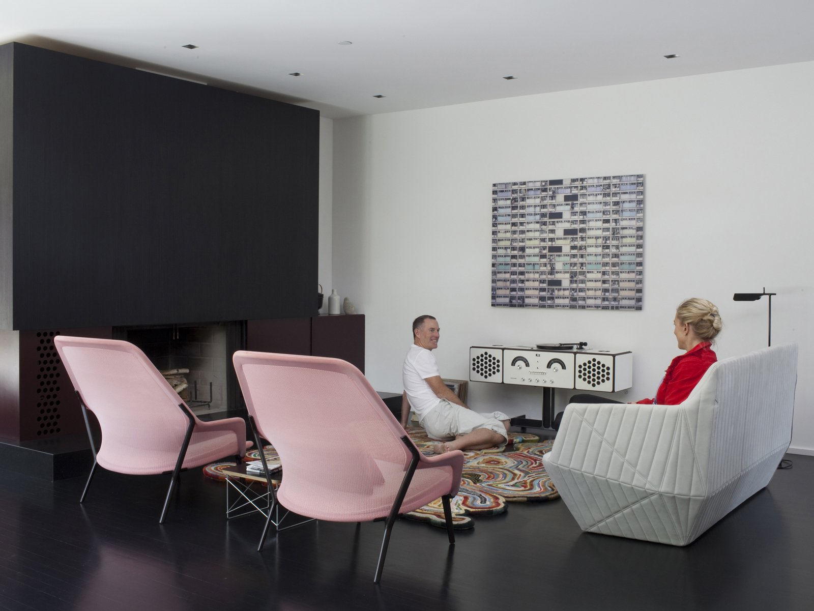 Living Room, End Tables, Rug Floor, Dark Hardwood Floor, Standard Layout Fireplace, Floor Lighting, Chair, Sofa, and Recessed Lighting The living room is home to two Bouroullec Brothers designs: the Facett sofa for Ligne Roset, and the Slow chair for Vitra.  Photo 29 of 33 in Designed In-House