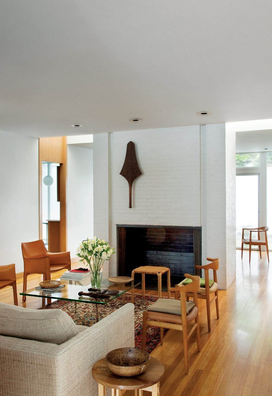 A club from the Fiji islands is mounted on the wall of the fireplace that divides the living and dining rooms. The dining room—furnished with two Cab chairs by Mario Bellini for Cassina, a pair of Cowhorn chairs by Hans J. Wegner for Johannes Hansen, the Barcelona Table by Mies van der Rohe for Knoll, and a Y61 stool by Alvar Aalto for Artek—has no windows, but lightwells on either side of the chimney provide brightness. Another design by Wegner, the Chair, peeks out from the dining room.  Photo 5 of 8 in The House of a Lifetime