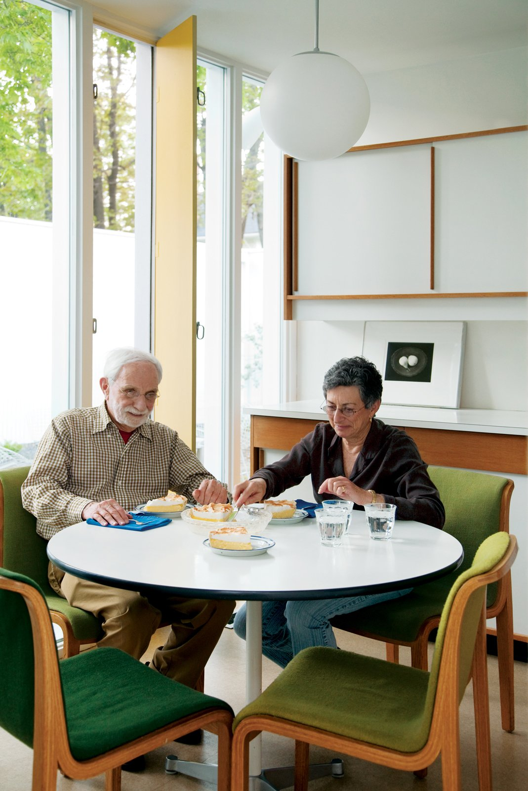 Isaacson and his best friend, Mary T. Hatch, snack at a dining table by Charles and Ray Eames for Herman Miller in the eat-in kitchen.  Photo 6 of 8 in The House of a Lifetime
