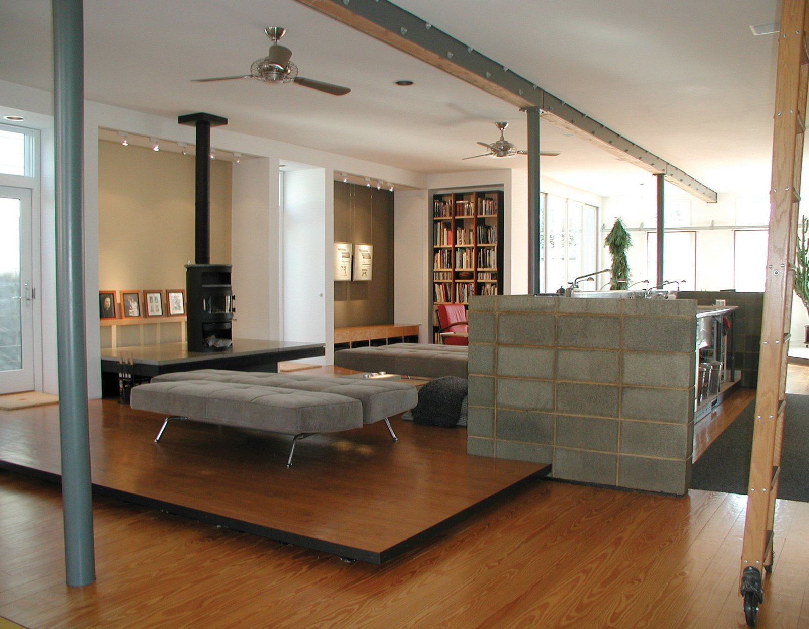 A floating platform defines the living zone and a concrete block wall surrounds a new commercial kitchen (a reference to the old store's huge penny candy counter).  Photo 15 of 30 in Triangle House Tours