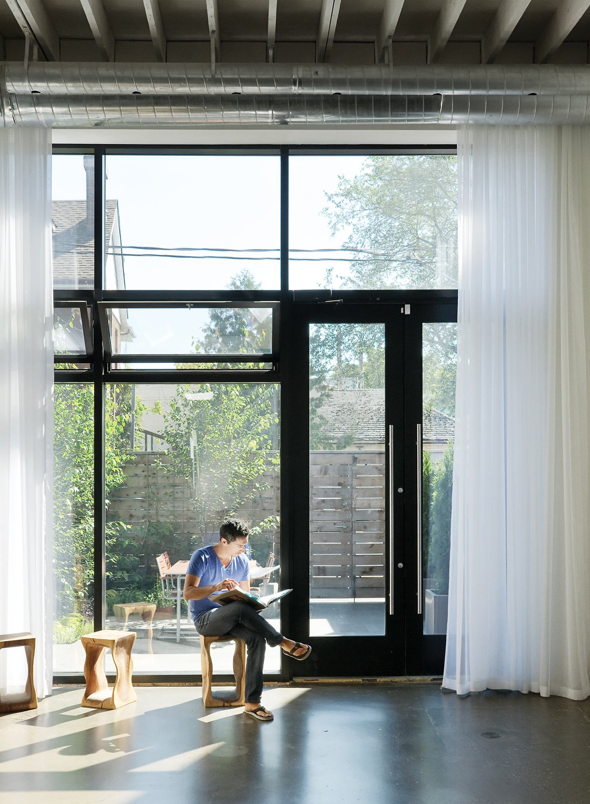 Windows and Metal In the house's front room Monkman relaxes on a stool from local retailer Andrew Richard Designs. A new window system draws in sunlight and views of the front courtyard designed by local landscape architect Terry McGlade, the building's former owner.  Photo 5 of 12 in 12 Striking Examples of Clerestory Windows in Modern Homes from An Art Studio That Would Make Picasso Jealous