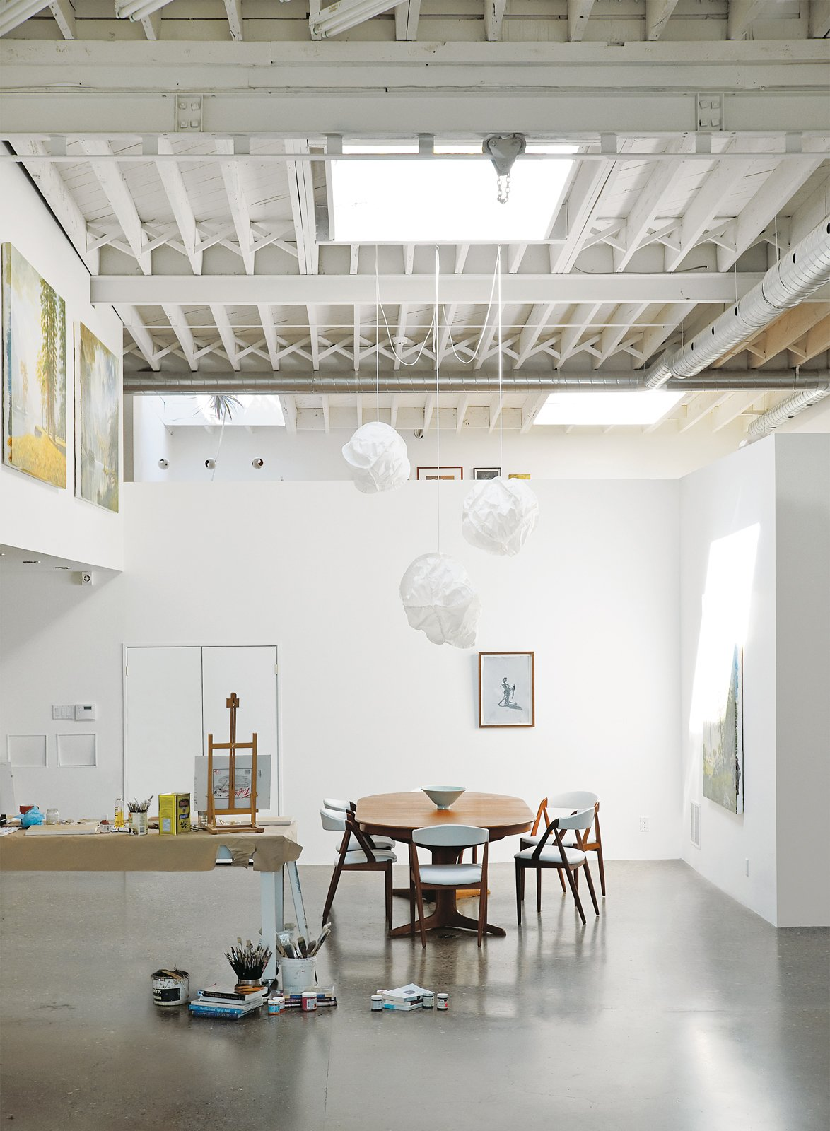 """Dining Room, Chair, Table, Pendant Lighting, and Concrete Floor Inside, white paint lightens up the middle of the building. A vintage Danish dining set and Cloud pendants by Frank Gehry for Vitra define the dining area.  Search """"classic danish nesting tables set"""" from An Art Studio That Would Make Picasso Jealous"""