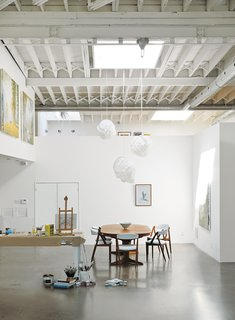 Inside, white paint lightens up the middle of the building. A vintage Danish dining set and Cloud pendants by Frank Gehry for Vitra define the dining area.