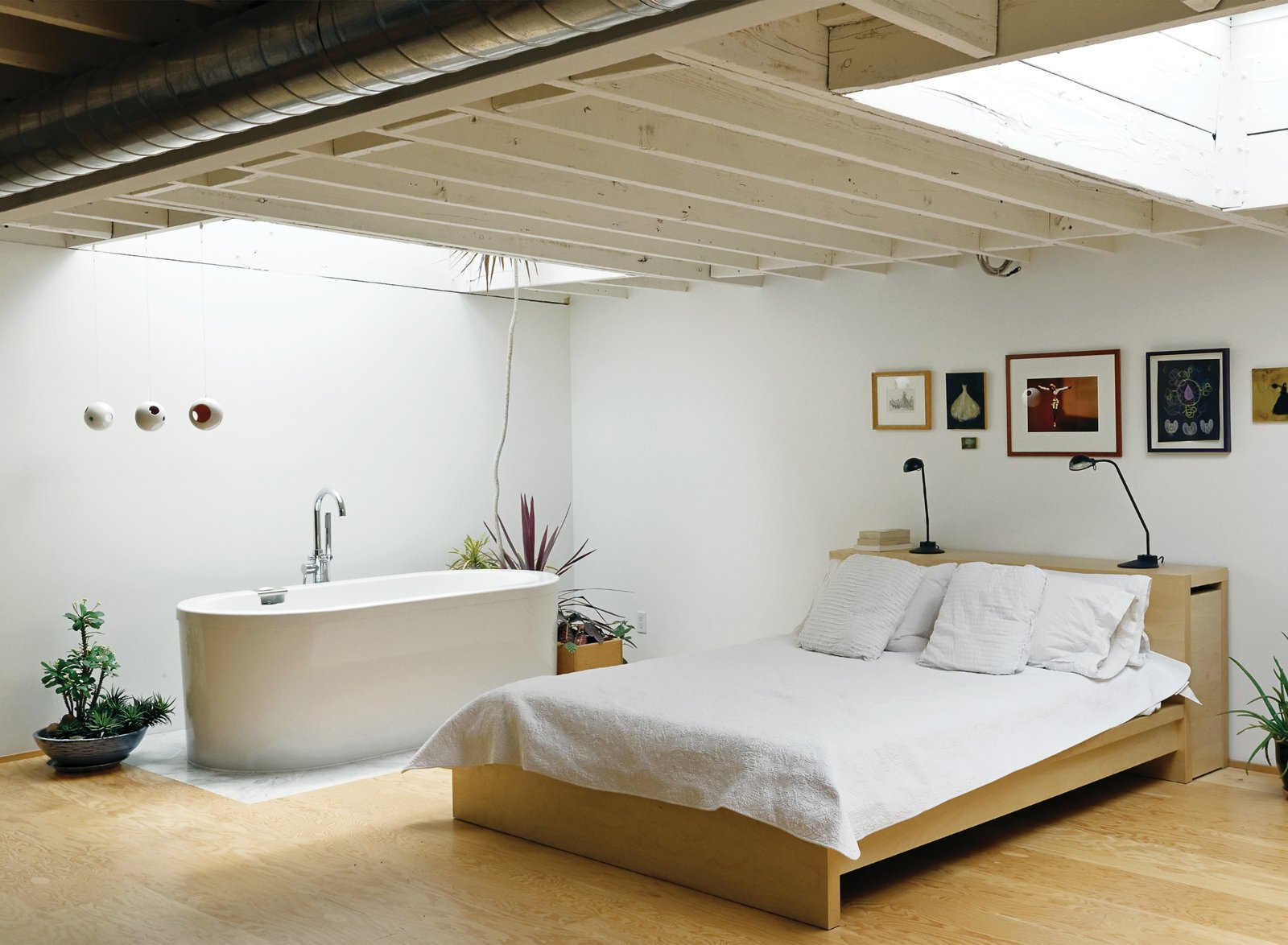The bedroom mixes a bed and lamps from Ikea with a deep, luxurious bathtub (an inexpensive model from Neptune). The artworks include original prints by New York artist Franco Mondini-Ruiz.  Spaces Transformed by Interior Plants by William Harrison from An Art Studio That Would Make Picasso Jealous
