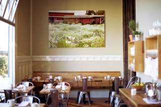 "At the end of the dining room, an image by Kelli Yon hangs above the counter. ""She's a local artist we like who traveled around this spring to photograph local farms,"" Bleskacek says. ""We tried to find something with a plow but we loved this beautiful picture of the old, dilapidated, red barn and the flowers in the front."""