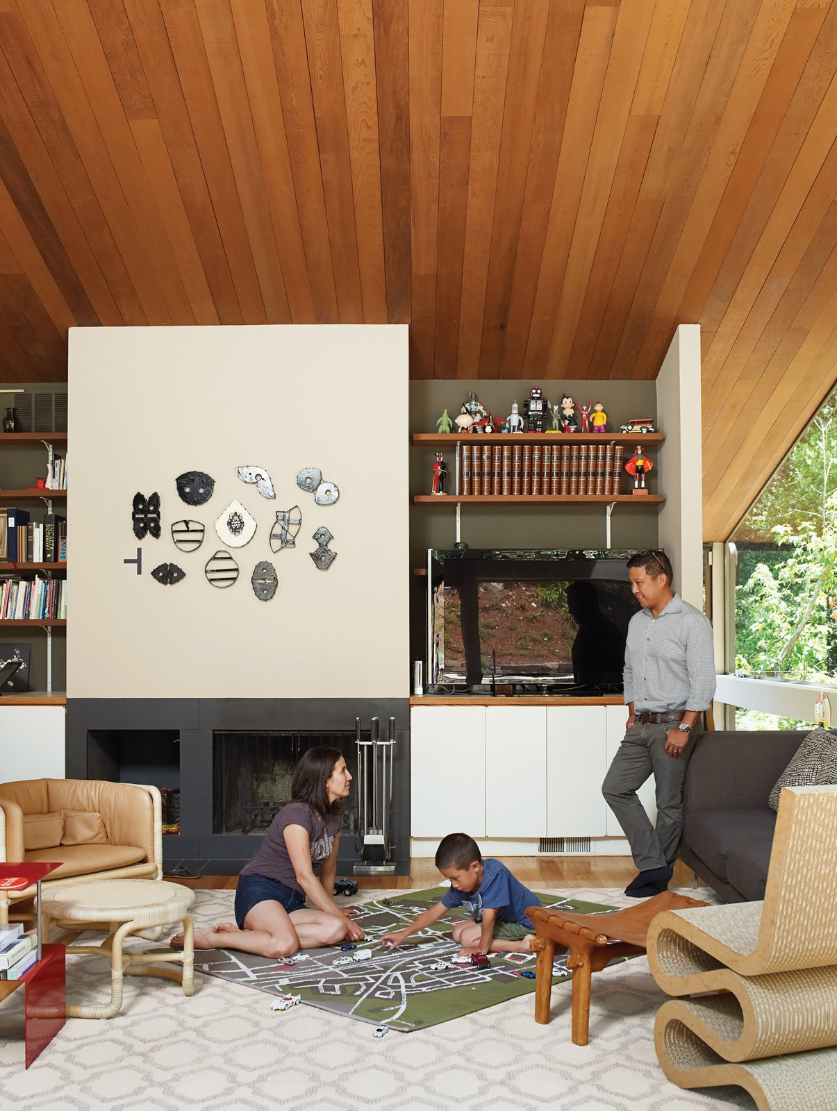 Living Room, Chair, End Tables, Light Hardwood Floor, Standard Layout Fireplace, Sofa, and Stools As his parents look on, Apolo plans his commute under a fire-top piece by the artist Michael Ricardo Andreev and alongside a Wiggle chair by Frank Gehry.  Photo 4 of 5 in A Pile of Scrap Cardboard Inspired Frank Gehry's Iconic Collection from Undivided Intentions
