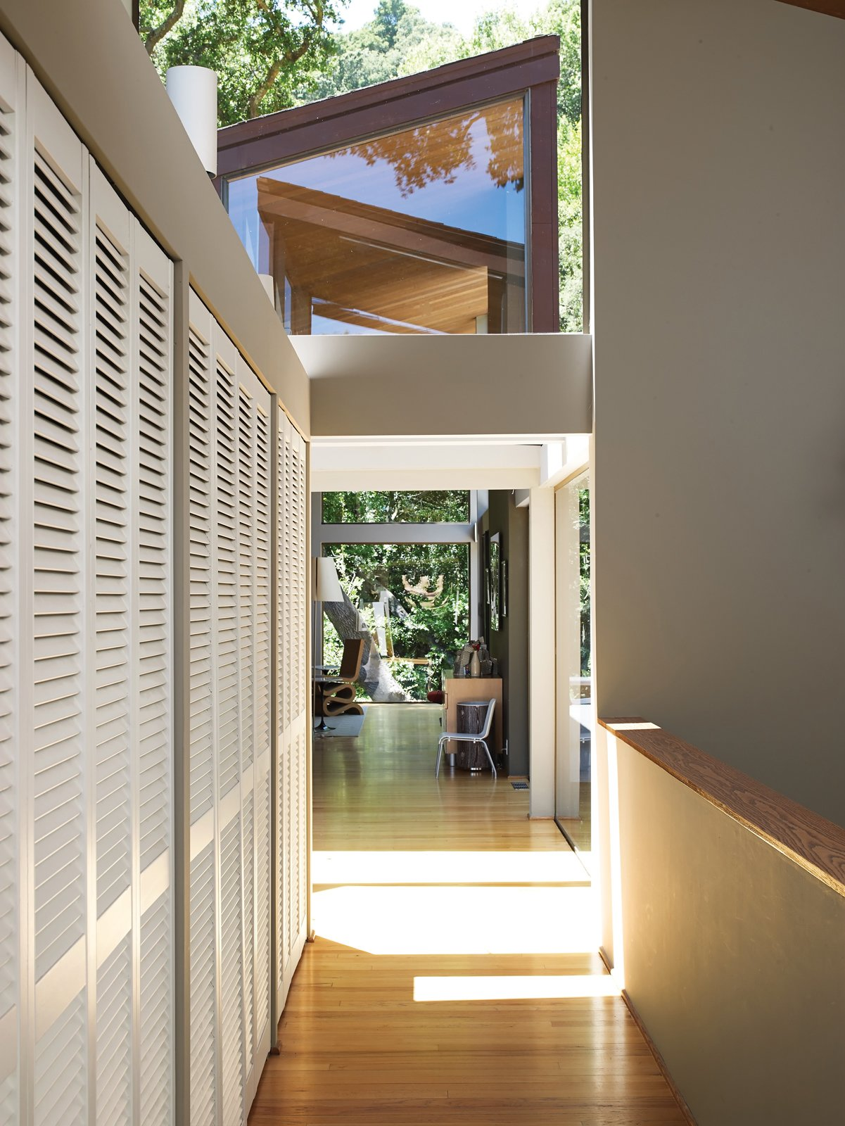 Hallway and Light Hardwood Floor The bridge leads from the living room to the bedrooms and from the studio to the garage.  Photo 7 of 19 in Undivided Intentions