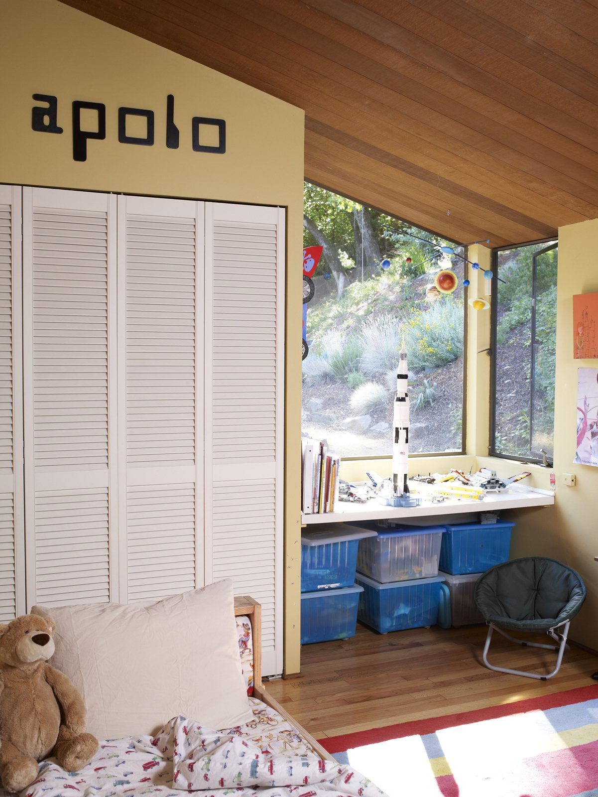 Kids, Bedroom, Bed, Chair, Storage, Desk, Boy, and Light Hardwood Apolo's bedroom is unmistakably that of a young boy, as the old-school computer font and clear debt to NASA suggest.  Kids Desk Boy Photos from Undivided Intentions