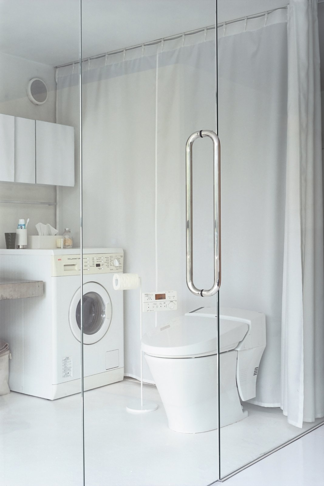 Laundry The bedroom and bath share a glass wall.  Best Laundry Photos from Small Space Live/Work Box Home in Japan