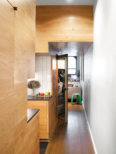 Kitchen, Wood Cabinet, Ceramic Tile Backsplashe, and Medium Hardwood Floor White oak paneling imbues uniformity and warmth into the hallway, kitchen, and living spaces.  Photo 4 of 12 in The Manhattan Transformation