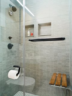 """I got rid of the bathtub because I like the idea of a big shower,"" Pozner explains. But to achieve a comparable effect, he installed a teak bench from Waterworks on the rear shower wall. ""One of the things I like about a bath is that you can soak. Here I can sit and have the water pound on me—it's a hybrid shower and bath."""