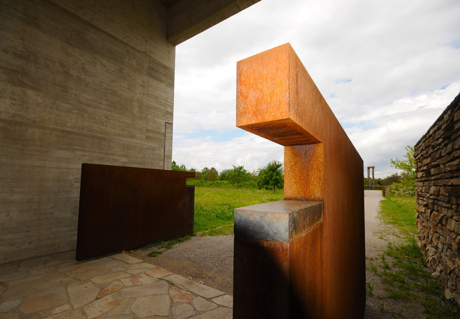 """Cor-Ten steel doors open to the gravel path that meanders through a flowering meadow to the cemetery.  Search """"cor ten steel"""" from A Modern Mortuary in Munich"""