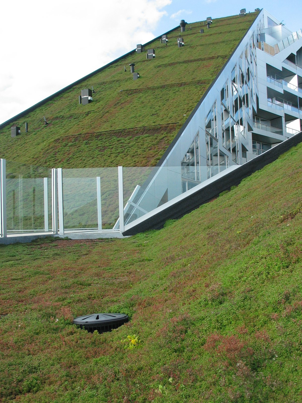 On two of the Eight House's sloping roofs are more than 2,000 square feet of green roofs. The goal was to reduce the urban heat island effect and increase the efficiency of the building as well as reference the farmlands and protected space to the south.  House by Bjarke Ingels Group by Miyoko Ohtake