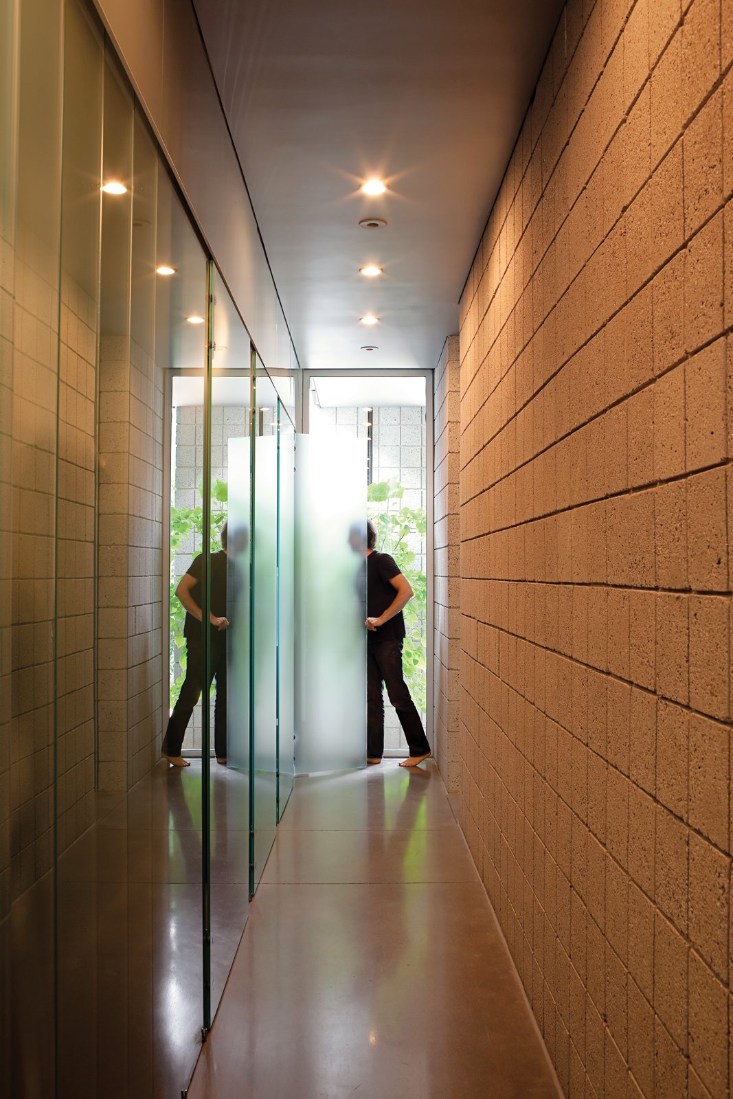 """Hallway Keener demonstrates how the translucent glass doors in the hallway pivot to create larger private spaces, like an expanded bathroom.  Search """"how bathrooms small spaces"""" from Startin' Spartan"""