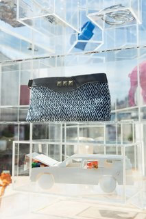 ViaPortal's Plexiglas shelves are purpose-built to show a changing collection: Miyakawa made this plastic model station wagon, and the Indigo Clutch by Article 22 was dyed and handwoven in Laos.