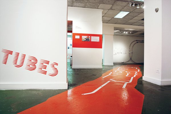 The exhibition graphics employ a customized headline typeface developed by Project Projects. The painted floor graphic shows the shape of Roosevelt Island (in orange) and the extent of the pneumatic tube system (in white).