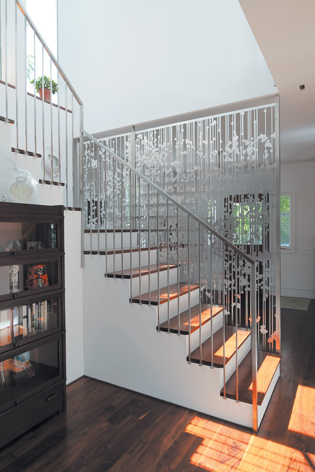 Staircase and Wood Tread Andrew Magnes's hanging screen composed of aluminum circles and lines, cut with a CNC water jet, separates the entry from the staircase and rear kitchen area.  Photo 9 of 11 in An 1850 Schoolhouse in Milford, Pennsylvania