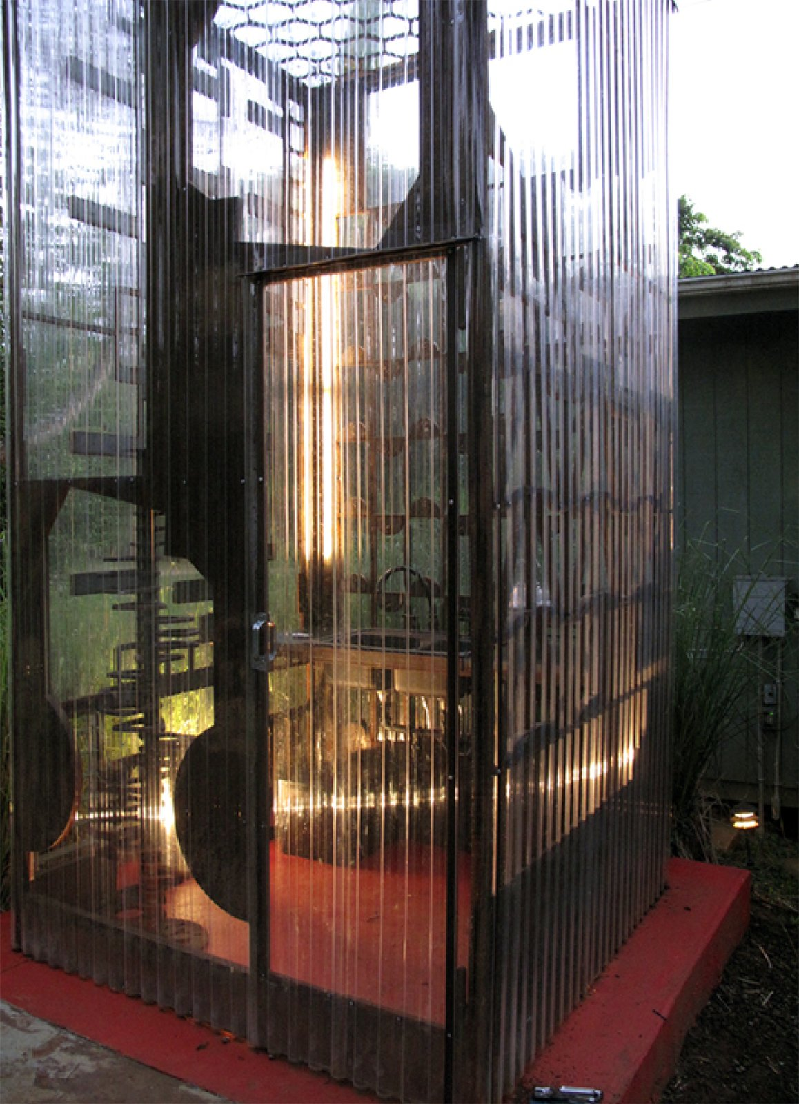"""A small door lets cooks and hungry interns into the Cor-Ten steel and corrugated polycarbonate tube.  Search """"cor ten steel"""" from Salvaged Jungle Kitchen"""