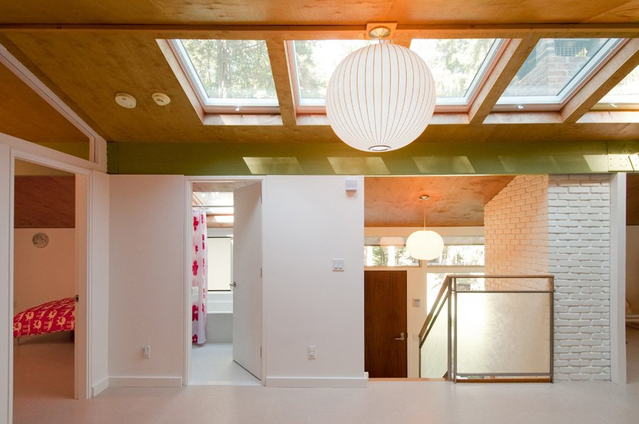 """The two twelve-by-sixteen-foot bedrooms, directly above a comparable pair on the first floor, feature a glass transom that follows the pitch of the roof. """"The stair and railings were very simple,"""" Depardon observes. """"We added a bit of design, with panels made from frosted Japanese rice paper between layers of glass."""" The architects created skylights and installed rooftop solar panels that heat the water and first-floor radiant system – changes Depardon considers faithful to Koch's philosophy of rationality and cost-effectiveness. """"The idea was, this is a great little piece of architecture – let's try to be respectful of it.""""  Show-Stealing Skylights in Modern Homes by Zachary Edelson from Techbuilt House"""