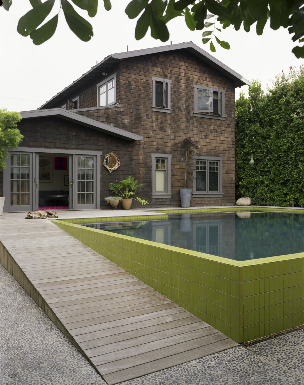 A seeded concrete walkway leads from the rear driveway—the entrance used most often—and into the yard. To create the look, each river rock was hand-placed in the wet concrete.  Modern Pool Design by Dwell from Master Stroke