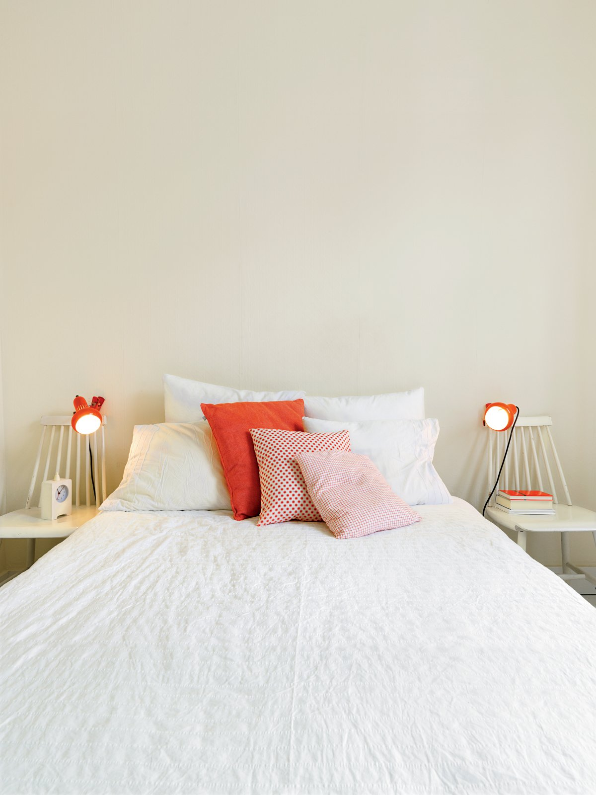 """Bedroom, Bed, and Table Lighting The orange his-and-hers lamps in the bedroom came from Högner's sister's childhood bedroom. """"My sister prefers new things,"""" said Högner. """"But my dad can't throw anything out.  Photo 9 of 15 in Kind of New"""