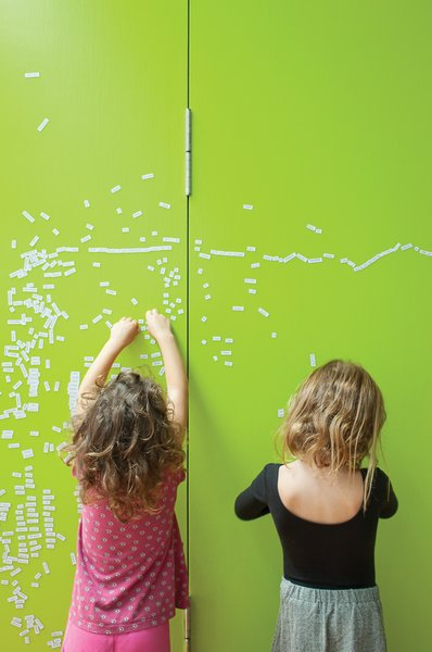 """The couple initially painted partition walls between the children's room and their own with black metallic paint creating both a writing surface for the children and a magnetic bulletin board for notes. However, """"the black looked too oppressive,"""" Astrakhan says. So they applied several coats of lively lime green paint to brighten up that section of the house."""