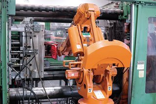 After the rPET mixture is heated and transformed via injection molding into a chair, a robotic arm removes it from the specially designed mold.