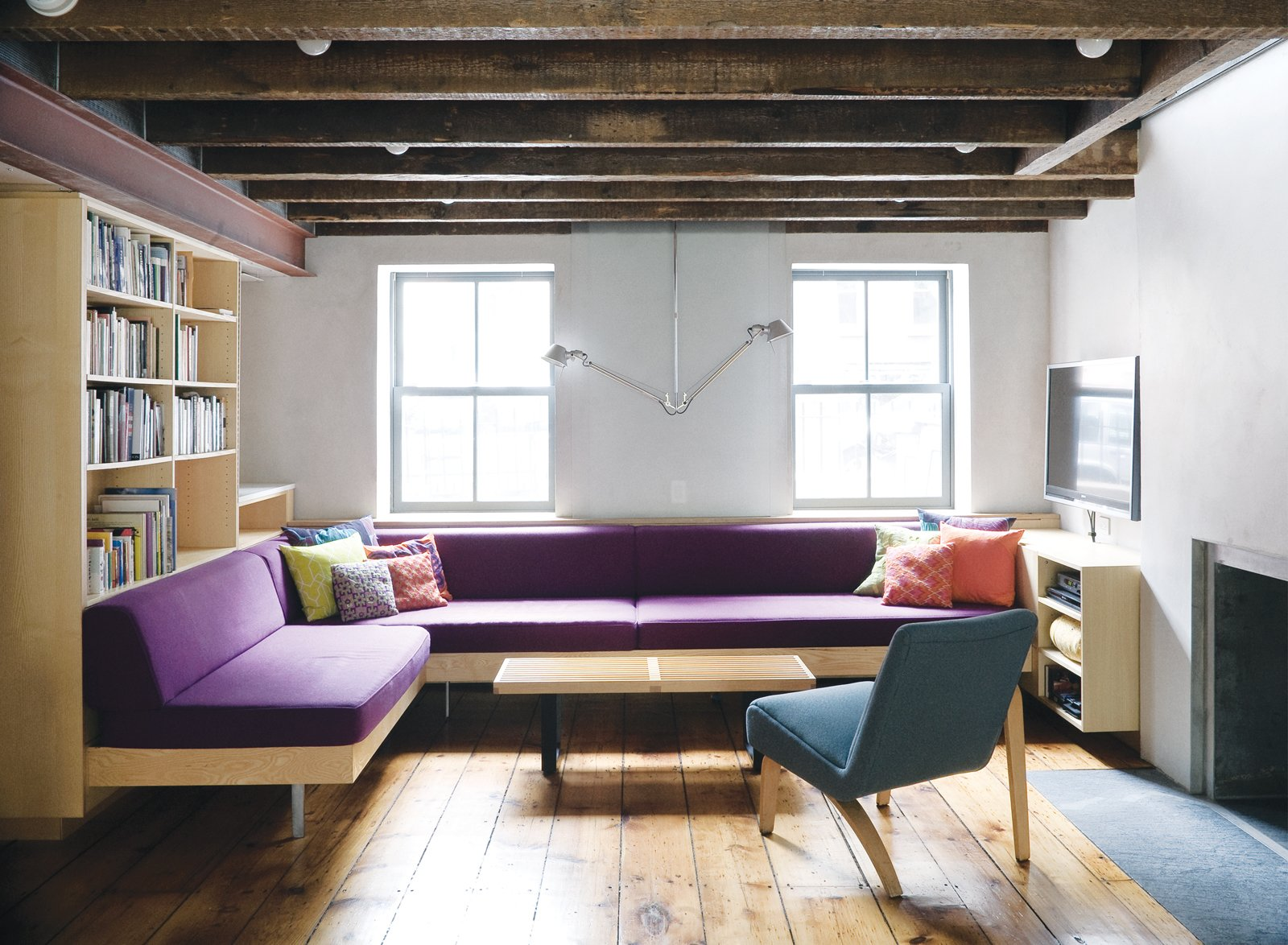 Facing the front facade on the English basement level, a sectional of Dixon's design punctuates the otherwise neutral hues with a stately purple. The lamp is a double-suspension Tolomeo from Artemide. The reupholstered Thonet chair lends balance to the room through its own asymmetry. Tagged: Living Room, Sectional, Medium Hardwood Floor, and Chair.  Photo 1 of 28 in Family Home Renovation in Brooklyn