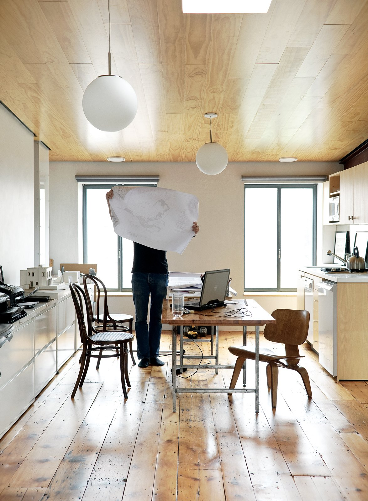 Kitchen and White Cabinet Dixon inspects a drawing in the couple's shared office on the home's top floor. The space features a sloping ceiling that rises to ten feet at one end. The new wood of the inserted ceiling counterpoints the vintage pumpkin pine floorboards underfoot.  Photo 3 of 28 in Family Home Renovation in Brooklyn