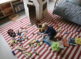Paul spreads out his toys on a rug from Pottery Barn.