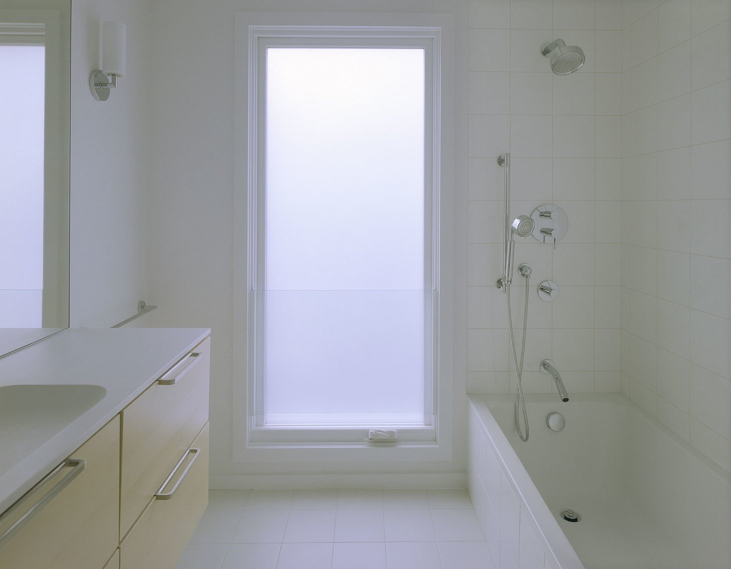 An IKEA vanity is suspended off the floor, making it easy to clean. The Spartan style and sense of space is enhanced here, as elsewhere in the home, by the oversized windows, white hues, and lack of architectural frippery or frills. Kohler shower fixtures complete the look. Photo: Atelier Waechter.  Portland's Cape Cod Remodel by Amara Holstein