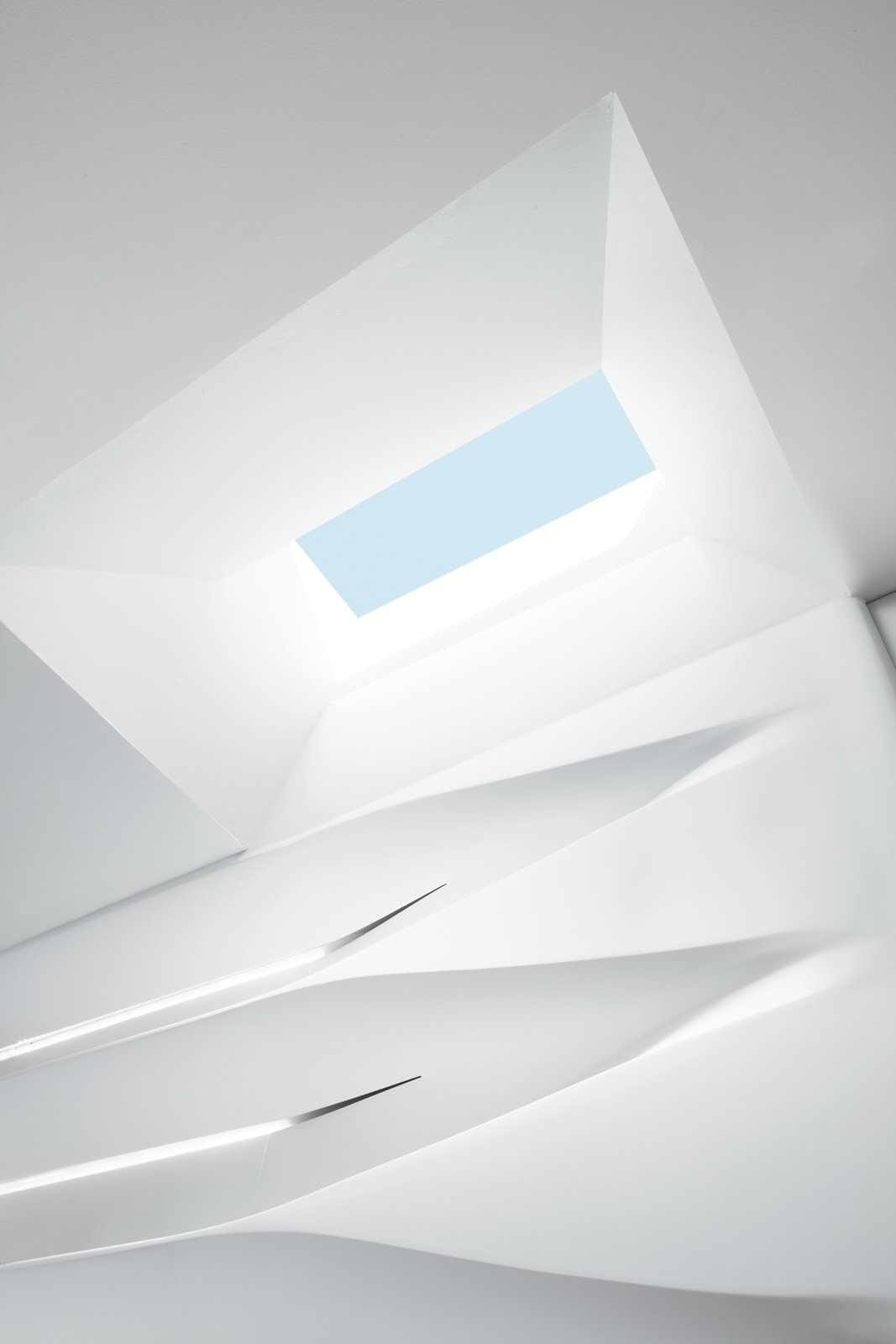 """The clients embraced the material because it is kidproof—any marks can be cleaned easily and the matte finish resists fingerprints. The structure was built off-site, brought into the apartment in pieces, installed on a wooden skeleton, and then sanded over a three-day period to achieve a seamless integration with the back wall and the skylight overhead. """"It's kind of a melting design that comes from above and goes down the shelves,"""" says Schoenenberger.  Photo 4 of 8 in All Together Now"""