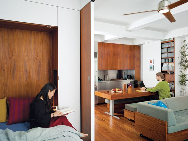 """Screened by the sliding door, Rosa cozies up with a book in the bedroom, while across the apartment Robert uses the hydraulic kitchen table as a work desk. """"We wanted to explore the power of custom design by creating integrated furniture to maximize both efficiency and aesthetics,"""" says Rosa."""