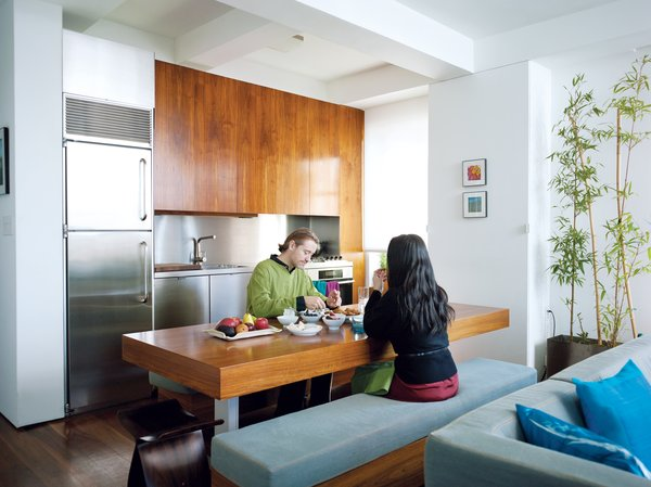 A New York City apartment with walnut upper kitchen cabinets has a stainless-steel backsplash that ties into the finish of the fridge and the lower cabinets. The walnut dining room table does quadruple duty as a work station and storage unit, and an eating and entertaining area.