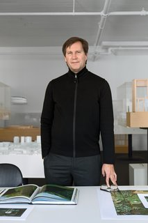 """Thomas Phifer stands in his west SoHo office and studio, with the firm's exquisitely crafted architectural models behind him. The room's all-white walls and ceiling are receptive to shadow and sunlight: """"I love turning out the lights here; you see the color of the walls changing all day long,"""" says Phifer."""