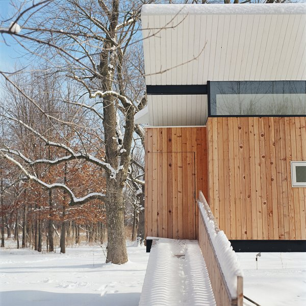 """Exterior, Cabin, Butterfly, and Wood A simple walkway leads to the unassuming entrance. """"It's obscured, detailed like the cedar walls,"""" Poss says. Photo by Phillip Kalantzis-Cope.  Best Exterior Butterfly Cabin Photos from Butterfly Roof Meditation Hut"""