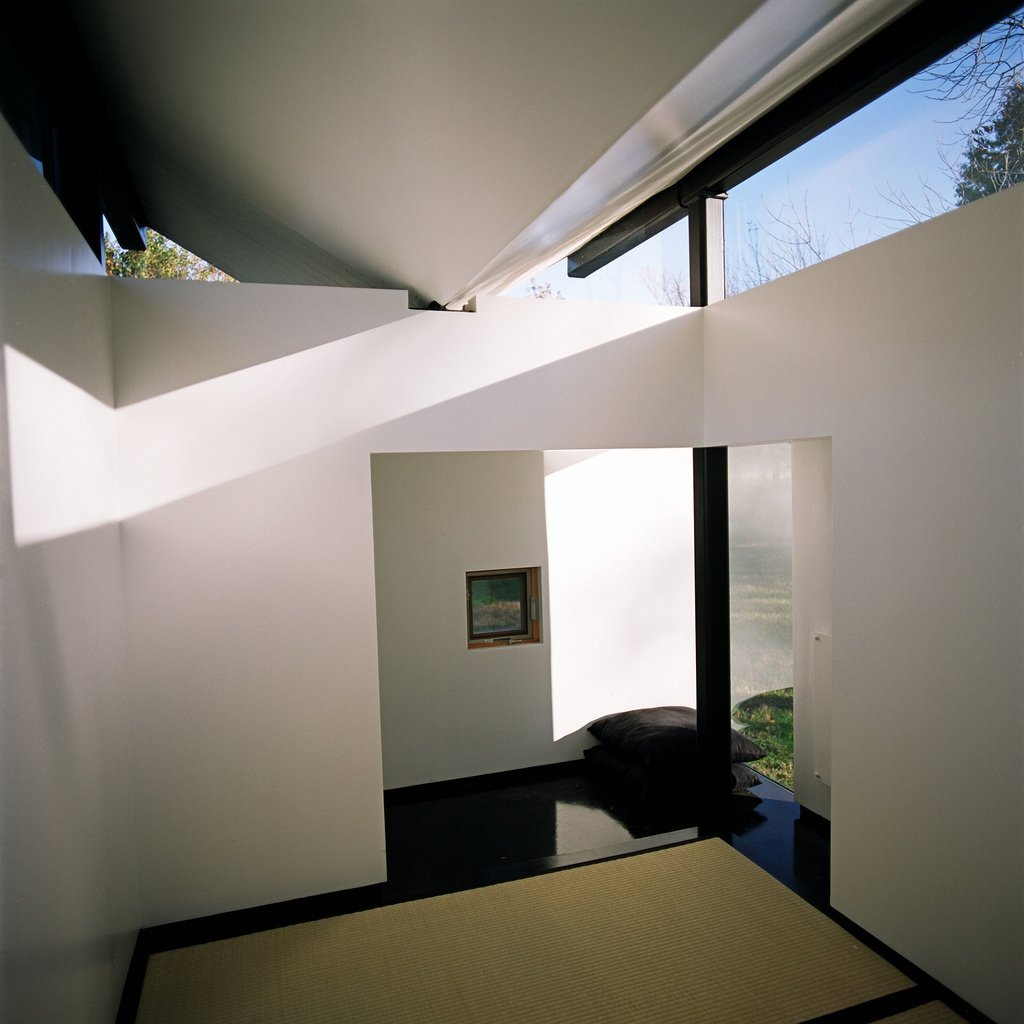 """Living Room and Rug Floor Inside, a large window opposite the main door frames a view of mature trees. The main interior spaces is the raised platform supporting three tatami mats. """"The floor of glossy ebonized birch has the sensation of a deep, still pond,"""" Poss says. """"The grass tatami mats become an island within an island."""" Photo by Phillip Kalantzis-Cope.  Butterfly Roof Meditation Hut by Miyoko Ohtake"""
