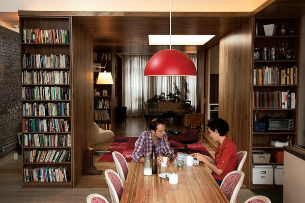 """Adrian Jones and Allison Silverman sit at their reclaimed wood dining table. Eco-mindedness is a matter-of-fact part of everyday life for the couple and the designer, Garrick Jones. """"Sustainability comes from flexibility and planning for the long term,"""" Garrick says. """"This is not a glammed-up loft."""""""